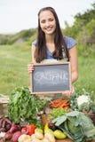 Nätt brunett som säljer organiska grönsaker Royaltyfri Foto
