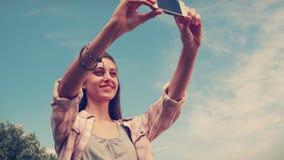 Nätt brunett som tar en selfie i parkera arkivfilmer