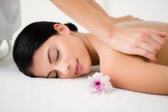 Nätt brunett som tycker om en massage med blomman royaltyfri foto