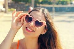 Nätt brunettkvinna i rosa hjärtalolitasolglasögon på stranden Ferier, semesterlopp och frihetsbegrepp H?rligt lyckligt arkivbilder