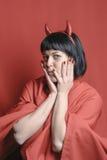 Nätt brunettkvinna med hornen för röd jäkel Royaltyfri Fotografi