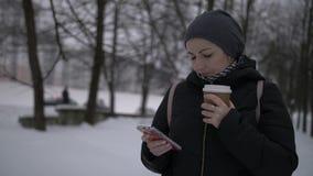 Nätt brunettkvinna på snödrinkkaffet och bruksmobiltelefonen, vinter arkivfilmer