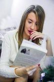 Nätt brunettläsning på soffan på jul ays och folkbegrepp - lycklig läsebok för ung kvinna hemma Arkivfoton