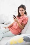 Nätt brunettsammanträde på hennes soffa genom att använda hennes smartphone Royaltyfri Fotografi