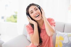 Nätt brunettsammanträde på hennes soffa som lyssnar till musik arkivbilder