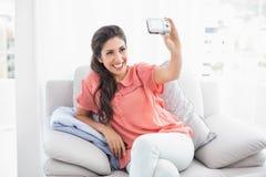 Nätt brunettsammanträde på hennes soffa som tar en bild av henne Arkivbilder