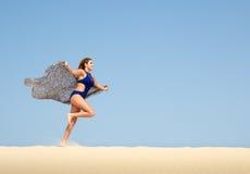 Nätt brunettspring i sanden Arkivfoto