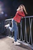 Nätt Caucasian kvinna i rött läderomslag och jeans royaltyfri bild