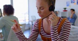 Nätt Caucasian kvinnlig ledare som talar på hörlurar med mikrofon på skrivbordet 4k arkivfilmer