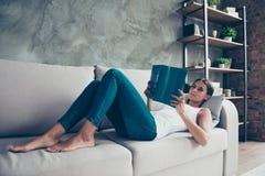 Nätt charmig kvinna i jeans som lägger på soffan som rymmer i hand Royaltyfri Fotografi