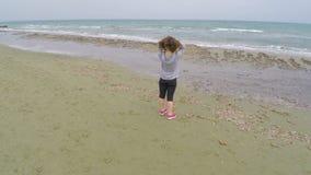 Nätt dam med lockigt hår som tycker om fantastisk sikt på havet som står på stranden stock video