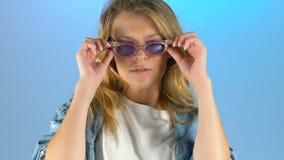 Nätt dam som av tar solglasögon och ser in i kamera med piercingögonkastet lager videofilmer