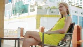 Nätt drömlik ung kvinna i gult klänningsammanträde i stol nära simbassäng i stad arkivfilmer