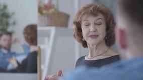 Nätt elegant mogen kvinna som talar med hennes partner som hemma sitter på soffaslutet upp Reflexion av två personer in arkivfilmer