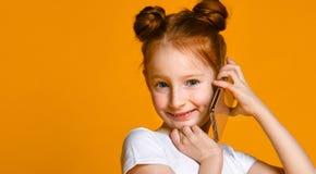 Nätt emotionell liten flicka som talar vid mobiltelefonen royaltyfria bilder