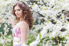 Nätt försiktig ung elegant härlig flicka med frodigt hår med en kant av ljust färgade blommor i en trädgård nära ett blomningträd Fotografering för Bildbyråer