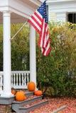 Nätt fallplats hemma med flaggan och pumpor Arkivbilder
