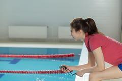 Nätt flicka för simninglagledarelagledare med stoppuren nära poolside Royaltyfri Bild