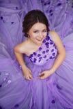 Nätt flicka i frodig lilaklänning royaltyfri foto