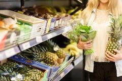 Nätt flicka i fruktmarknad med olika färgrika nya frukter och grönsaker olivgrön för olja för kök för kockbegreppsmat ny över häl Royaltyfria Bilder