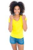 Nätt flicka i gula varma flåsanden för tshirt som och för grov bomullstvill hurrar på kameran Arkivbilder