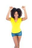 Nätt flicka i gula varma flåsanden för tshirt som och för grov bomullstvill hurrar på kameran Royaltyfri Fotografi