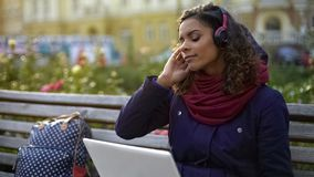 Nätt flicka i hörlurar som utomhus tycker om atmosfär av den favorit- musikbandkonserten royaltyfria foton