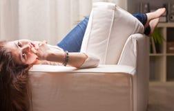 Nätt flicka i jeans som håller ögonen på dig från en soffa royaltyfri fotografi