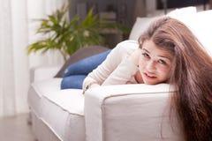 Nätt flicka i jeans som håller ögonen på dig från en soffa arkivbilder