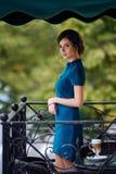 Nätt flicka i klassiskt anseende för elegant klänning på terrassen av sommarkafét som går att dricka kaffe Arkivbild
