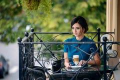 Nätt flicka i klassiskt sammanträde för elegant klänning på terrassen av sommarkafét som går att dricka kaffe arkivfoton