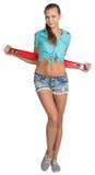 Nätt flicka i kortslutningar och röd skjorta som rymmer Fotografering för Bildbyråer