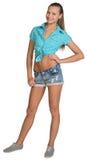 Nätt flicka i kortslutningar och skjortaanseende med handen Royaltyfri Bild