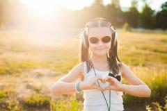 Nätt flicka i lyssnande musik för solglasögon Arkivfoto