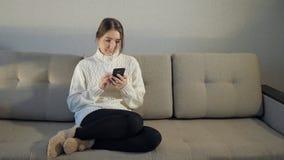 Nätt flicka i tröjan som sitter på soffan och att läsa meddelanden på telefonen lager videofilmer