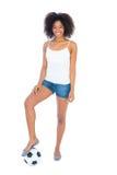 Nätt flicka i vitöverkant och varma flåsanden för grov bomullstvill med fotboll Arkivfoto
