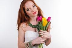 Nätt flicka med buketten av färgrika tulpan Royaltyfri Bild