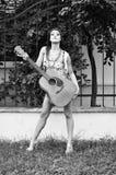 Nätt flicka med en gitarr utomhus Royaltyfri Bild