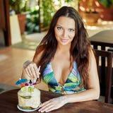 Nätt flicka med kokosnötcoctailen i stången Arkivbild