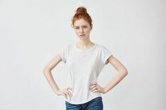 Nätt flicka med ljust rödbrun hår som ser kameran med akimbo armar Arkivbilder