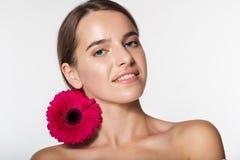 Nätt flicka med perfekt hud och den röda blomman Arkivbilder