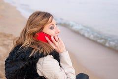 Nätt flicka med telefonen på stranden Royaltyfri Foto