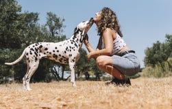 Nätt flicka och en lycklig dalmatian hund arkivbilder