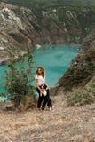Nätt flicka och svartvit sjö för beiside för hundborder collie stag i berg i kanjon royaltyfria bilder