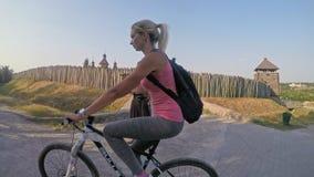 Nätt flicka på cykeln förbi fästningen arkivfilmer