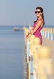 Nätt flicka på semester I som står på en pir som tycker om solsken Arkivfoton