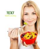 Nätt flicka som äter fruktsallad royaltyfria bilder