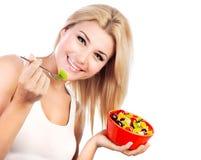 Nätt flicka som äter fruktsallad royaltyfria foton