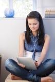 Nätt flicka som använder tableten och hörlurar med mikrofon arkivbilder