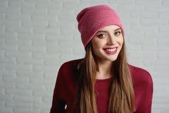 Nätt flicka som bär det rosa locket på den gråa bakgrunden arkivfoto